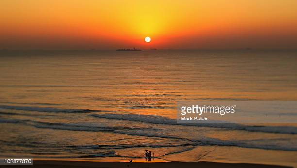 A baptism is performed as the sunrises over the Indian Ocean on June 19 2010 in Durban South Africa