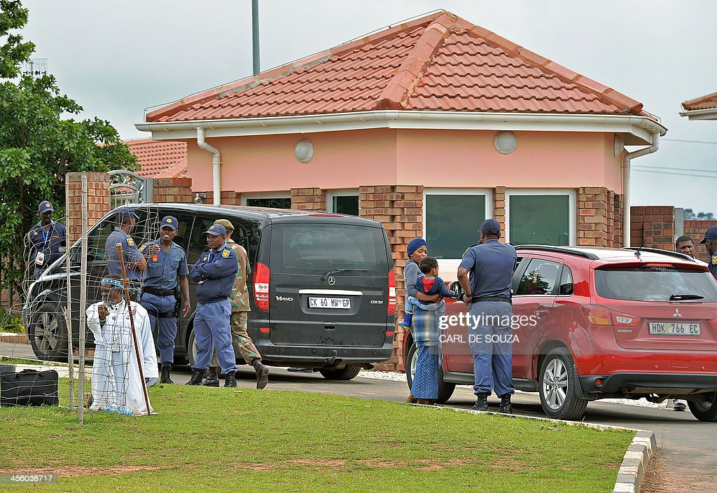 Baptist Priest Michael Nothynga kneels outside Nelson Mandela's former home in Qunu during a practice run ceremony on December 13, 2013. South African troops lined the road to Nelson Mandela's burial site in his boyhood home at Qunu, as preparations for his funeral got under way Thursday. Mandela, the revered icon of the anti-apartheid struggle in South Africa and one of the towering political figures of the 20th century, died in Johannesburg on December 5 at age 95. AFP PHOTO/Carl de Souza