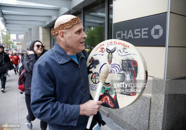 Baptiste Le Beau of the Cheyenne River Sioux and Lummi Tribes plays a drum as indigenous leaders and climate activists disrupt business at a Chase...