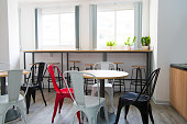 Bar counter at wall and tables with colorful chairs in canteen. Modern coworking space with furniture. Cafe concept