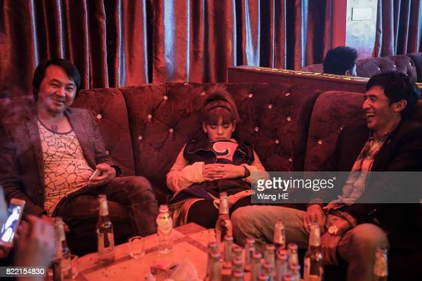 A bar girl is asleep as guests laugh in Tibetan Bar on July 22 2017 in Litang County southwest of Garze Tibetan Autonomous Prefecture Sichuan China...