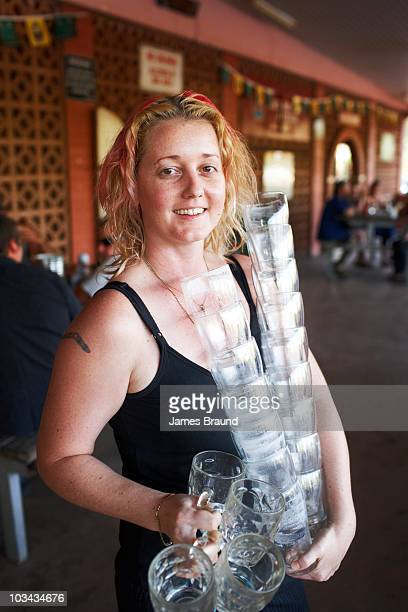 Bar maid with pile of beer glasses