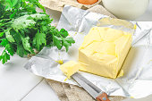 A bar of butter is cut into pieces on a wooden board with a knife, surrounded by milk, eggs and parsley on a white table. Ingredients for cooking