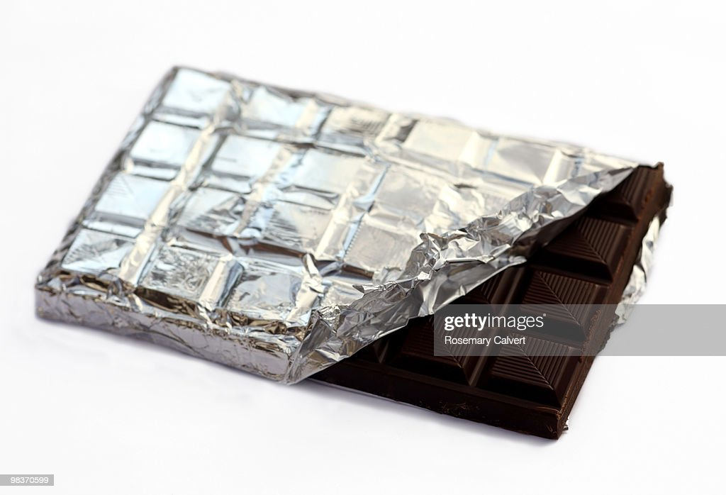 Bar of dark rich chocolate with foil. : Stock Photo