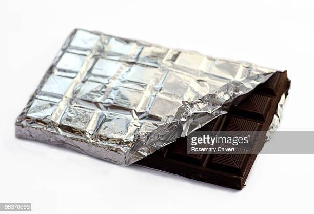 Bar of dark rich chocolate with foil.
