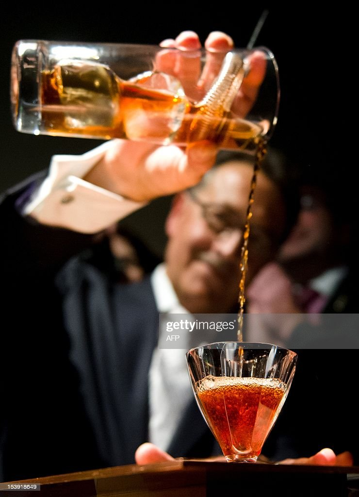Bar owner Salvatore Calabrese, pours a glass of 'Salvatore's Legacy', during an attempt to make the world's most expensive cocktail after mixing it at 'Salvatore's Playboy Club' in London, England on October 11, 2012. The event was attended by officials from the Guiness Book of World Records as Calabrese mixed the cocktail priced at GBP £5,500 (6,824 Euros) per glass and containing 40ml 1778 Clos de Griffier Vieux Cognac, 20ml 1770 Kummel Liqueur, 20ml circa 1860 Dubb Orange Curacao and two dashes of circa 1900s Angostura Bitters, in an attempt to beat the previous record held by 'The Skyview Bar' in Dubai who's cocktail cost GBP £3,766.52 (4,673 Euros) a glass.
