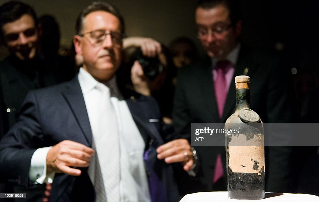 Bar owner Salvatore Calabrese prepares to open a bottle of 1778 Clos de Griffier Vieux Cognac ahead of mixing a glass of his 'Salvatore's Legacy' cocktail, during an attempt to make the world's most expensive cocktail at 'Salvatore's Playboy Club' in London, England on October 11, 2012. The event was attended by officials from the Guiness Book of World Records as Calabrese mixed the cocktail priced at GBP £5,500 (6,824 Euros) per glass and containing 40ml 1778 Clos de Griffier Vieux Cognac, 20ml 1770 Kummel Liqueur, 20ml circa 1860 Dubb Orange Curacao and two dashes of circa 1900s Angostura Bitters, in an attempt to beat the previous record held by 'The Skyview Bar' in Dubai who's cocktail cost GBP £3,766.52 (4,673 Euros) a glass. AFP PHOTO / LEON NEAL