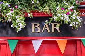 Bar sign with flowers and irish flag colors, irish pub concept in Dublin, Ireland