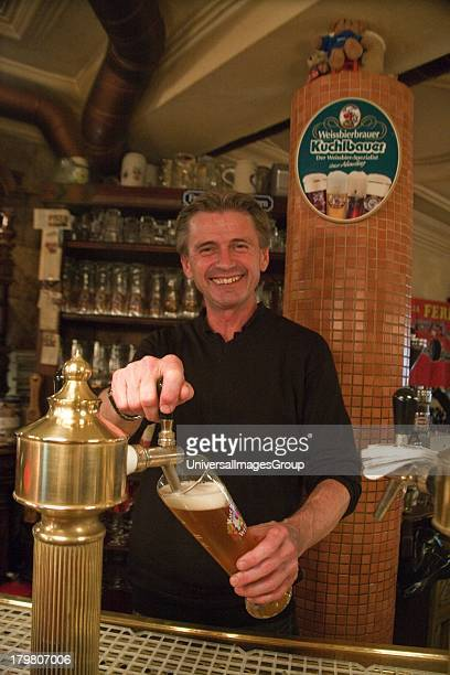 Bar tender at historic Dicker Mann brew house in Old Town Regensburg Germany an UNESCO World Heritage Site