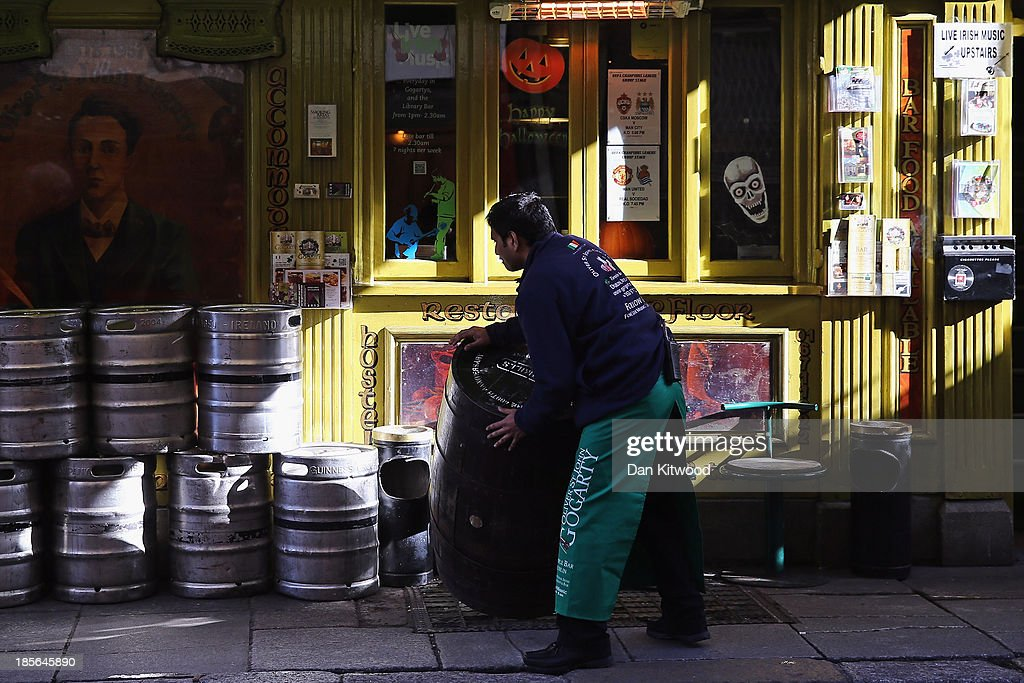 A bar worker moves barrels outside a pub in the Temple Bar area on October 23, 2013 in Dublin, Ireland. Dublin is the capital city of The Republic of Ireland situated in the province of Leinster at the mouth of the River Liffey. The greater Dublin area has a population of around 1.5 Million people.