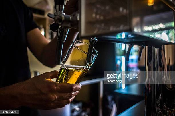 A bar worker pours a glass of cider from a tap at a cider bar in Prague Czech Republic on Thursday June 4 2015 A generation after communism's demise...