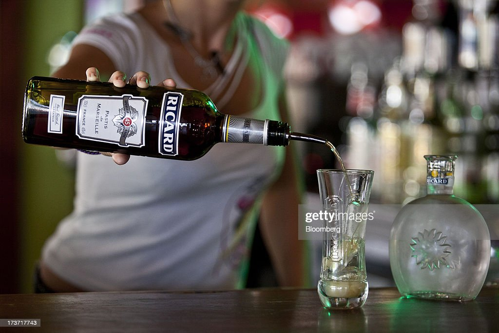 A bar worker pours a glass of Ricard pastis, produced by Pernod-Ricard SA, in this arranged photograph at a bar near Archacon, France, on Tuesday, July 16, 2013. Distillers such as Diageo and Pernod Ricard SA are seeking to expand in emerging markets where booming economic growth is creating a burgeoning middle class with more disposable income. Photographer: Balint Porneczi/Bloomberg via Getty Images
