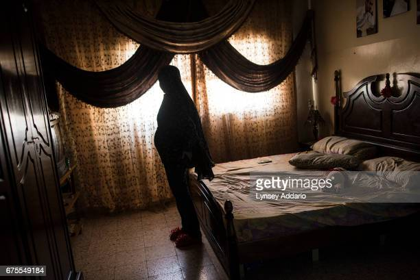 Bara'ah a Syrian refugee from Ghouta in the Damascus suburbs poses for a portrait six months pregnant in the room where she and her husband live in...