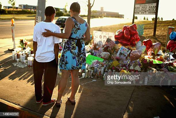 Barb Whitfield and her granson Wanya Whitfield visit at a makeshift memorial to the vicitims of last weekend's mass shooting at the Century 16 movie...