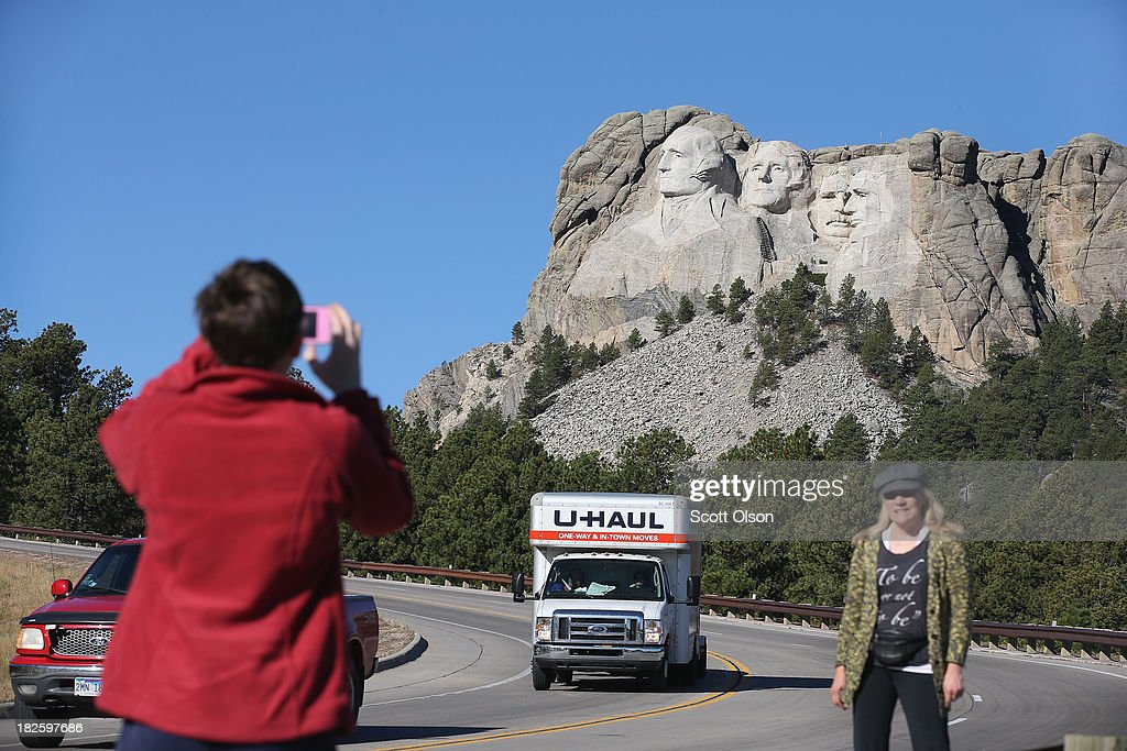 Barb Wleklinski (R) and her daughter Danielle stop to take a picture near the entrance to Mount Rushmore National Memorial on October 1, 2013 in Keystone, South Dakota. Barb was helping Danielle relocate from Illinois to Oregon and hoped to visit the memorial but, Mount Rushmore and all other national parks were closed today after congress failed to pass a temporary funding bill, forcing about 800,000 federal workers off the job. A bulletin issued by the Department of Interior states, 'Effective immediately upon a lapse in appropriations, the National Park Service will take all necessary steps to close and secure national park facilities and grounds in order to suspend all activities ...Day use visitors will be instructed to leave the park immediately...'