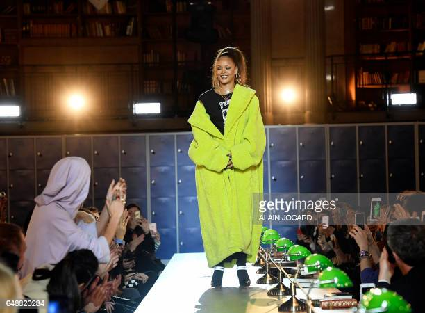 TOPSHOT Barbadian singer Rihanna is applauded by English fashion model Cara Delevingne during Rihanna's Fenty Collection from PUMA women's FallWinter...