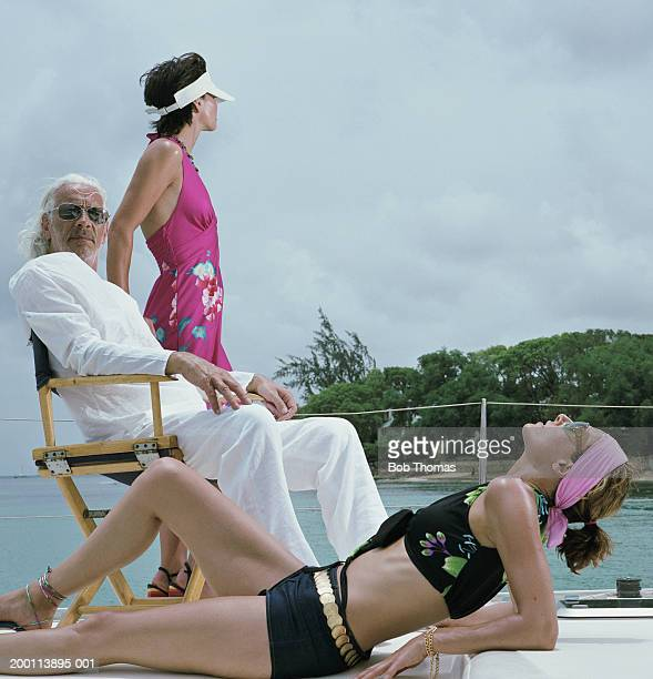 Mature man and two young women relaxing on boat