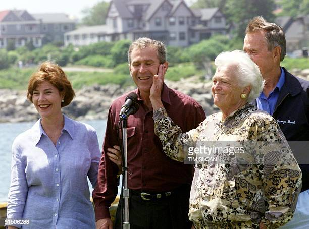 Barbara Bush playfully slaps his son Texas Governor George W Bush during a photo op at the family home with wife Laura and father former President...