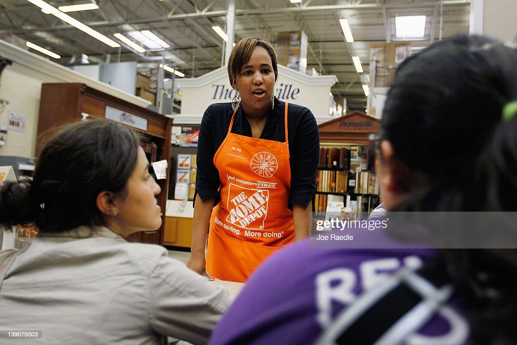 Barbara Chico (C), who was recently hired by The Home Depot, talks with customers while continuing her training to be a Home Depot Associate on February 16, 2012 in Miami, Florida. The Home Depot company announced that it will be hiring 70,000 new seasonal workers as U.S. unemployment claims have fallen to their lowest level in four years.