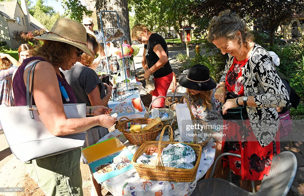 Barbara Davis left buys some baked goods from Polly Dicker right at the neighborhood's Pop Up Farm stand at the intersection of East 7th Avenue and...