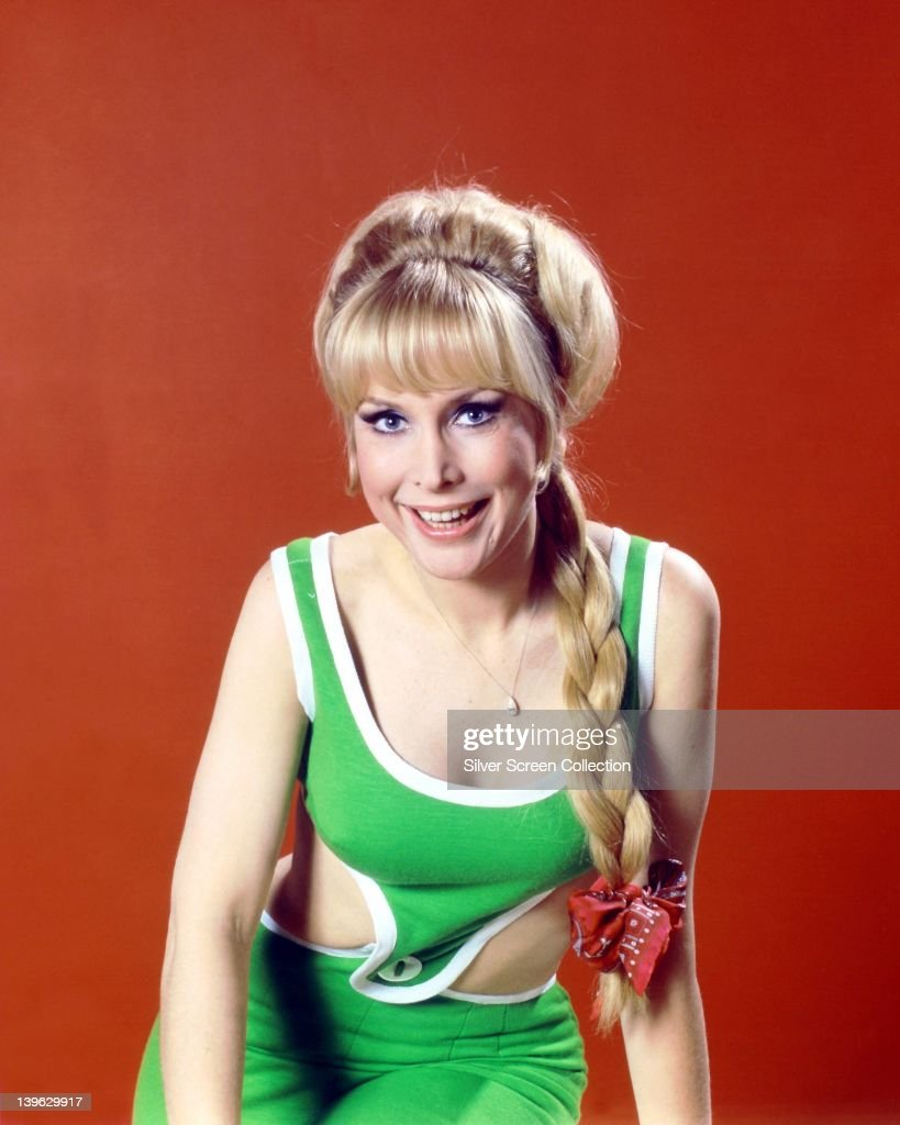 <a gi-track='captionPersonalityLinkClicked' href=/galleries/search?phrase=Barbara+Eden&family=editorial&specificpeople=206974 ng-click='$event.stopPropagation()'>Barbara Eden</a>, US actress, wearing a green and white outfit, smiling with her hair plaited, with a red bow, in a studio portrait, against a red background, circa 1965.