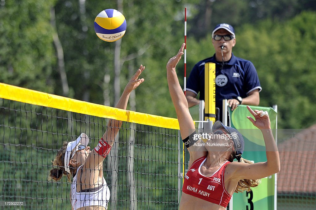 Barbara Hansel (R) of Austria attacks against Nadine Zumkehr (L) of Switzerland during Day 2 of the FIVB World Championships on July 2, 2013 in Stare Jablonki, Poland.