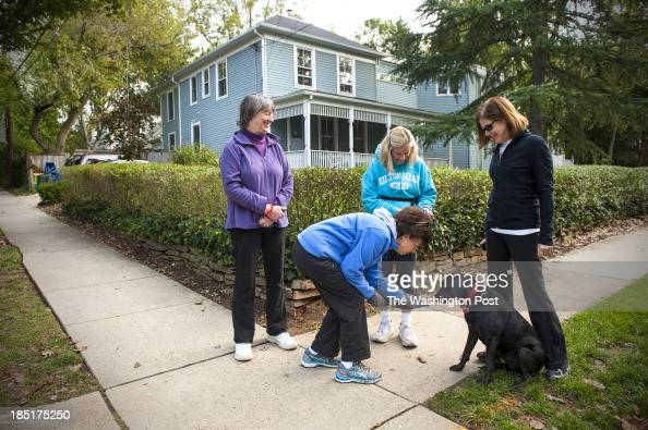 Barbara Marenus who has lived in the neigborhood 24 years offers a treat to Lady as an informal group of walkers from left Gail Schwartz a 47year...