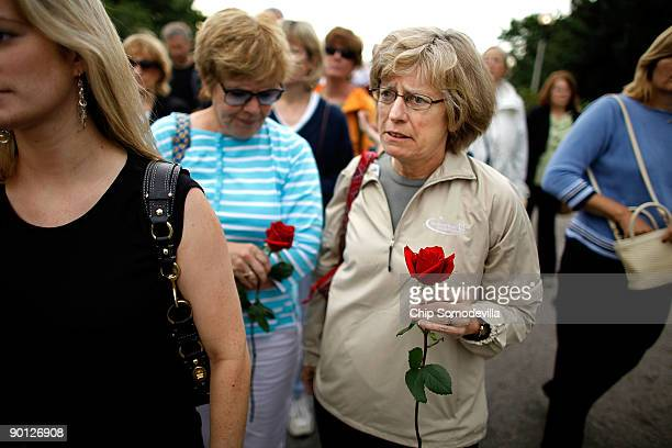 Barbara Ryan of Sudbury Massachusettes holds a red rose while waiting in line with her family to see Sen Edward Kennedy lie in repose at the John F...