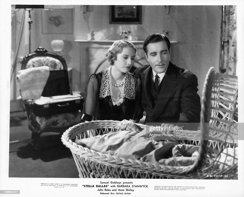Barbara Stanwyck and John Boles looking at baby in crib in a scene from the film 'Stella Dallas' 1936