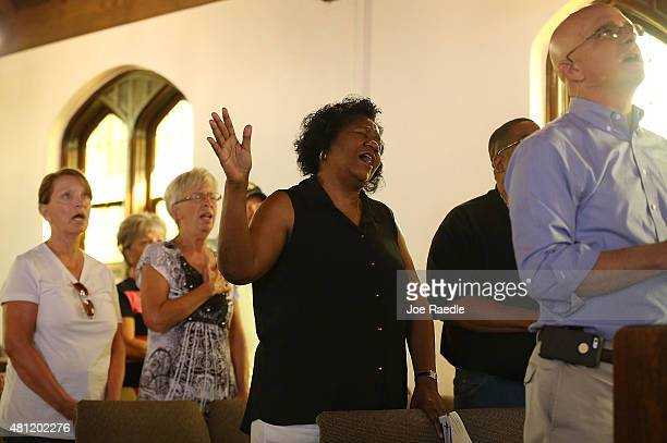 Barbara Woods joins others for prayer during a memorial service at the Chattanooga Church to honor the four Marines and on Navy sailor killed during...