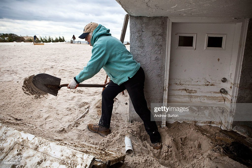 Barbara Young digs sand out from her front door, which was caused by Hurricane Sandy, on October 31, 2012 in Long Beach, New York.The storm has claimed many lives in the United States and has caused massive flooding across much of the Atlantic seaboard. U.S. President Barack Obama has declared the situation a 'major disaster' for large areas of the U.S. east coast, including New York City, with widespread power outages and significant flooding in parts of the city.