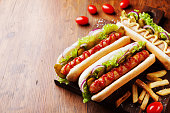 Barbecue grilled hot dog with sausage and yellow mustard with ketchup on wooden board. Traditional american fast food.