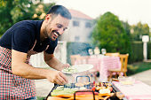 Smiling young chef making barbecue for his friends