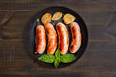 Barbecue sausages in frying pan on wooden table,top view