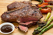A close up shot of a barbecued porterhouse steam grilled vegetables and some steak sauce.