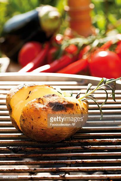 Barbecued potato on barbecue, vegetables in background