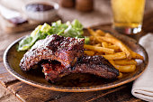 A plate of delicious barbecued ribs with french fries and salad.