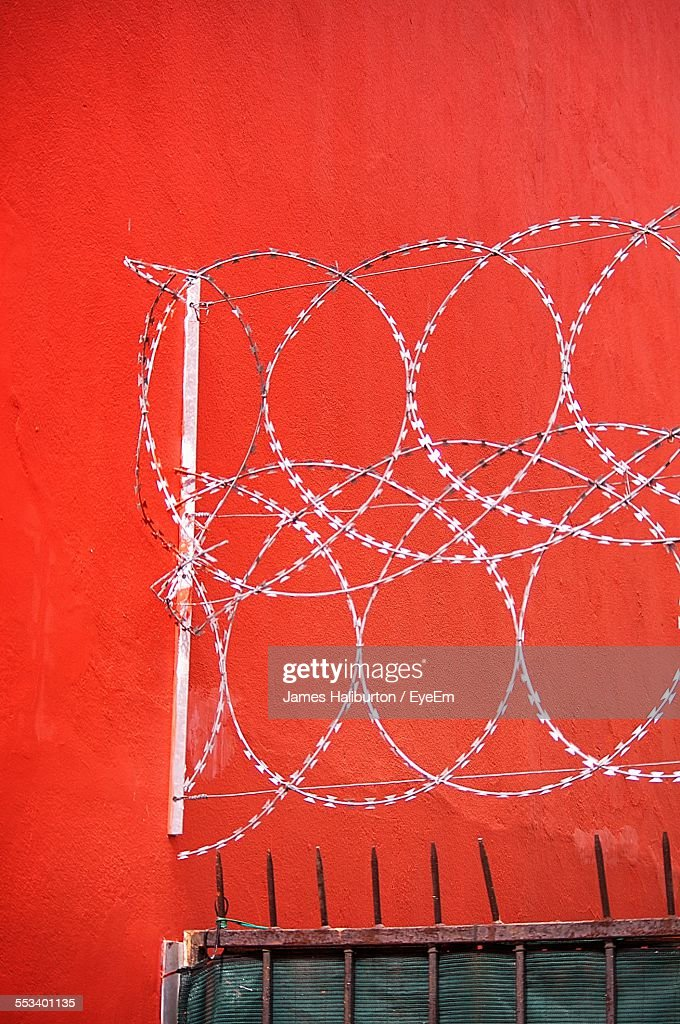 Barbed Wire Against Red Wall