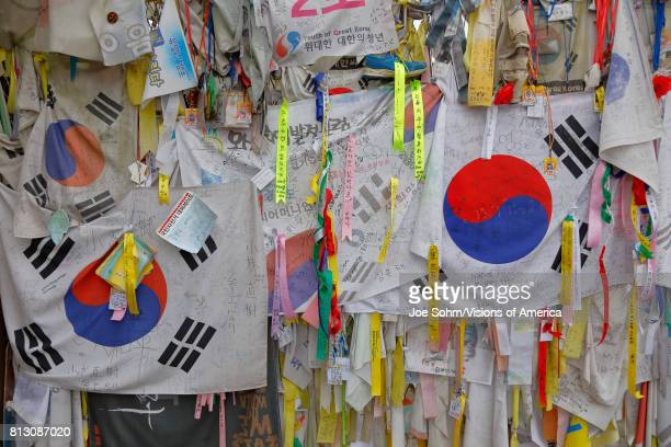 Barbed wire fence separates South from North Korea South Korean flags and prayer wishes attached to fence for those separated or who had died during...