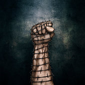 3D illustration of grungy raised fist wrapped in barbed wire against dark stone background