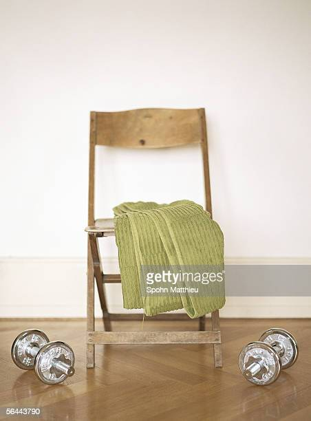 Barbells on floor next to chair with towel