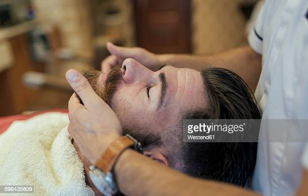 Barber adjusting beard of a customer