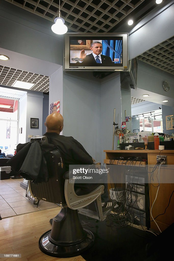 Barber Antonio Coye watches a television from his barber chair at the Hyde Park Hair Salon as U.S. President <a gi-track='captionPersonalityLinkClicked' href=/galleries/search?phrase=Barack+Obama&family=editorial&specificpeople=203260 ng-click='$event.stopPropagation()'>Barack Obama</a> takes the oath of office to officially start his second term on January 20, 2013 in Chicago, Illinois. Obama would get his hair cut at The Hyde Park Hair Salon, which is near his Chicago home, before he was elected to the White House. Chief Justice John Roberts administered the official swearing-in today and a public ceremony will take place January 21.