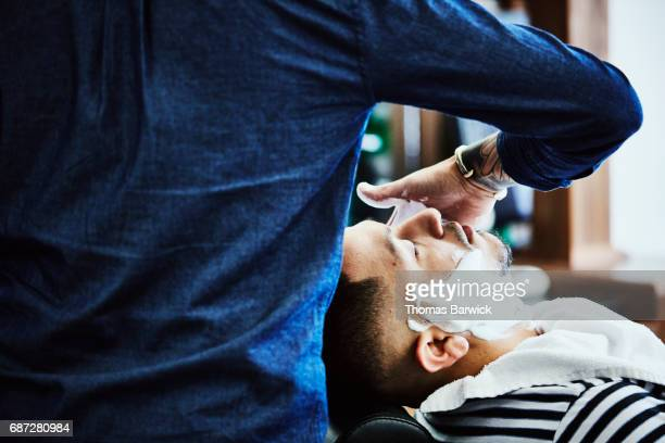 Barber applying shaving cream to client seated in barbers chair