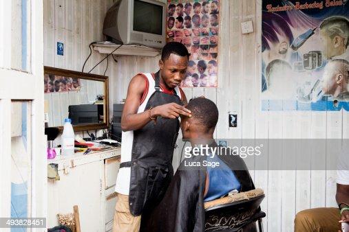 Barber at work in West Africa : Foto de stock