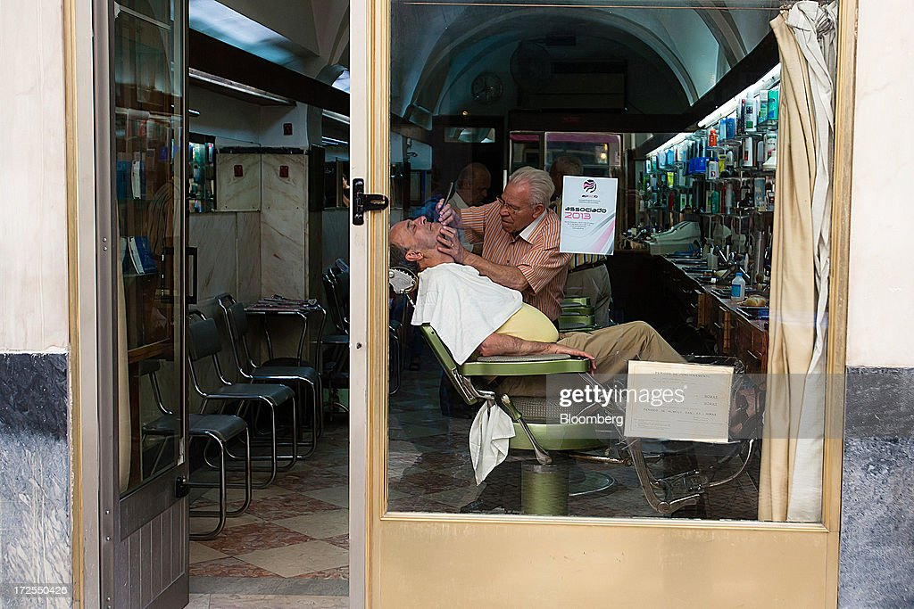 A barber attends his client at a barber shop in Lisbon, Portugal, on Wednesday, July 3, 2013. Portuguese borrowing costs topped 8 percent for the first time this year after two ministers quit, signaling the government will struggle to implement further budget cuts as its bailout program enters its final 12 months. Photographer: Mario Proenca/Bloomberg via Getty Images