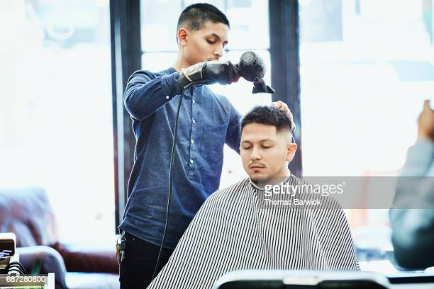 Barber blowing out clients hair with hair dryer after hair cut
