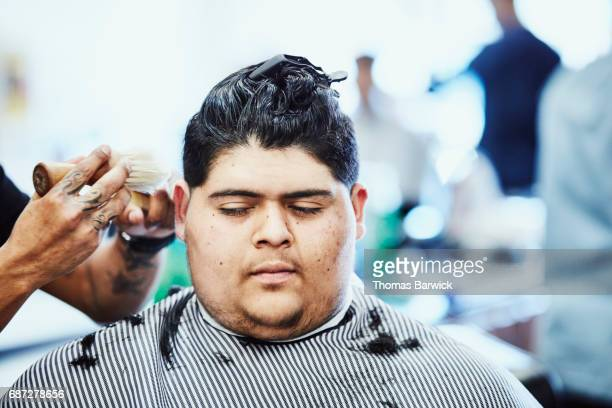 Barber brushing away hair clippings on man having hair cut in shop