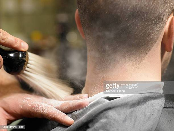 Barber brushing man's neck, close-up, rear view
