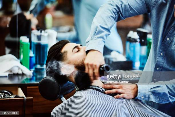 Barber brushing powder on clients neck after shave in barber shop